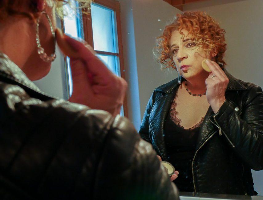 Auf dem Bild ist Jacqueline zu sehen, die vor einem Spiegel steht und Puder aufträgt.